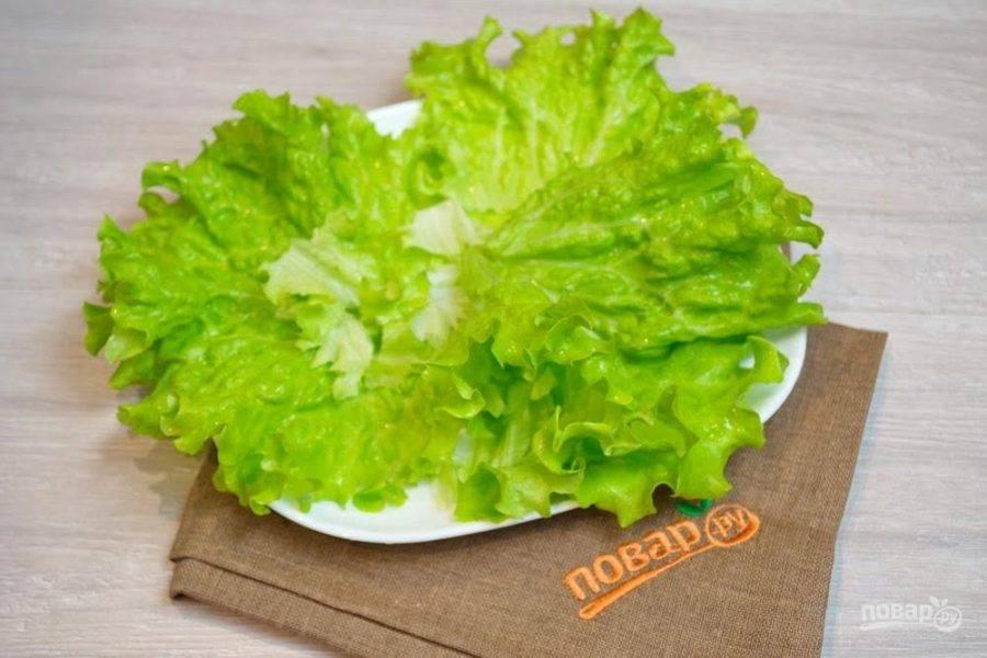 1. Для приготовления салата отварите перепелиные яйца в кипящей воде 4 минуты. Остудите и очистите. Салатные листья промойте под проточной водой. Обсушите. Уложите на подготовленное блюдо. В этом блюде мы и будем подавать салата.