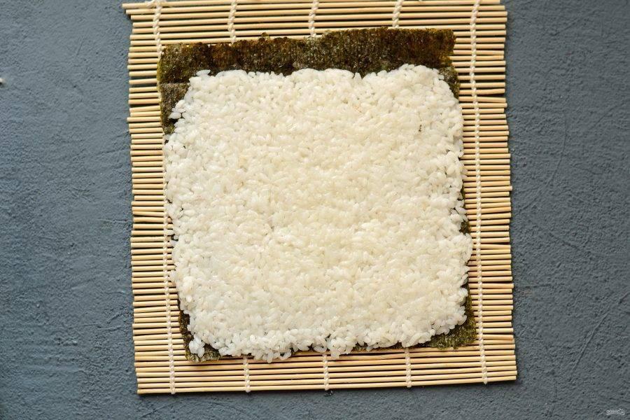 Положите лист нори шершавой стороной вверх. Выложите рис, оставив 2 см. свободным.