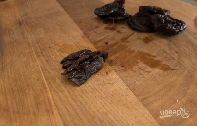 3.С чернослива слейте воду, нарежьте каждый тонкими полосками, добавьте его к ребрам, туда же отправьте обжаренный до мягкости лук.