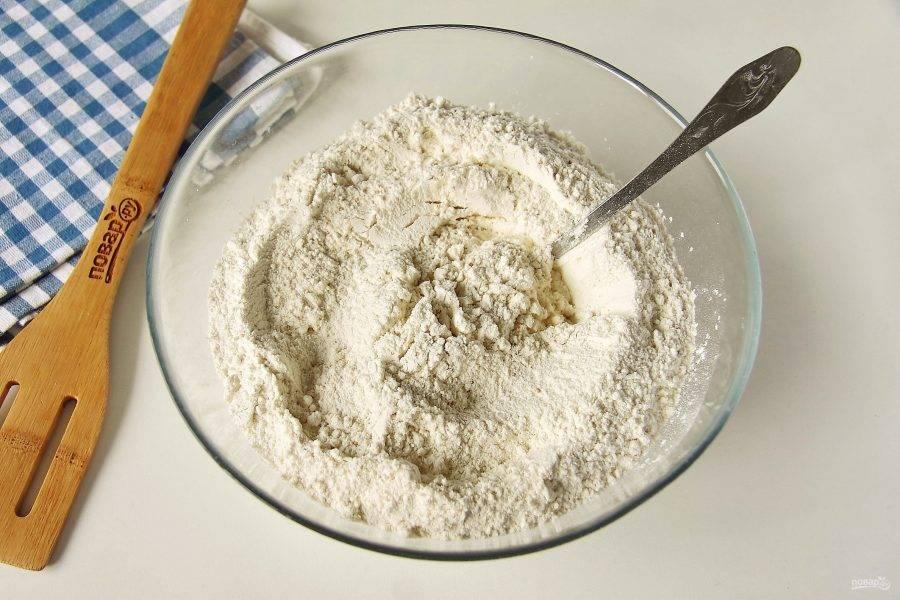 В глубокой миске соедините муку, дрожжи, соль и сахар.