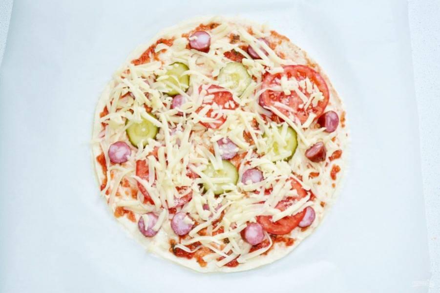 Выложите охотничьи колбаски, огурчик, помидоры. Присыпьте щедро тертым сыром.