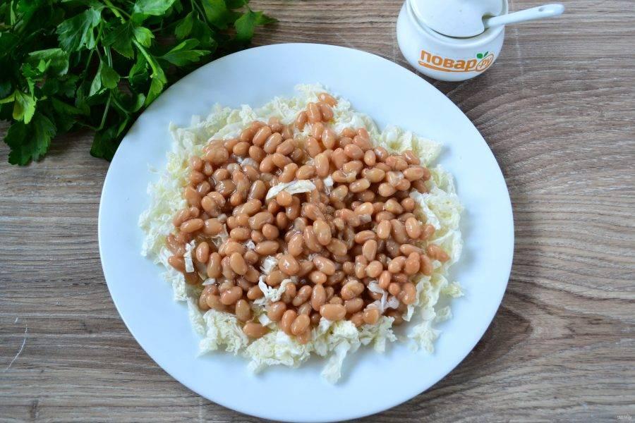 На большую плоскую тарелку выложите сначала капусту, чуть присолите ее, сверху выложите консервированную фасоль.