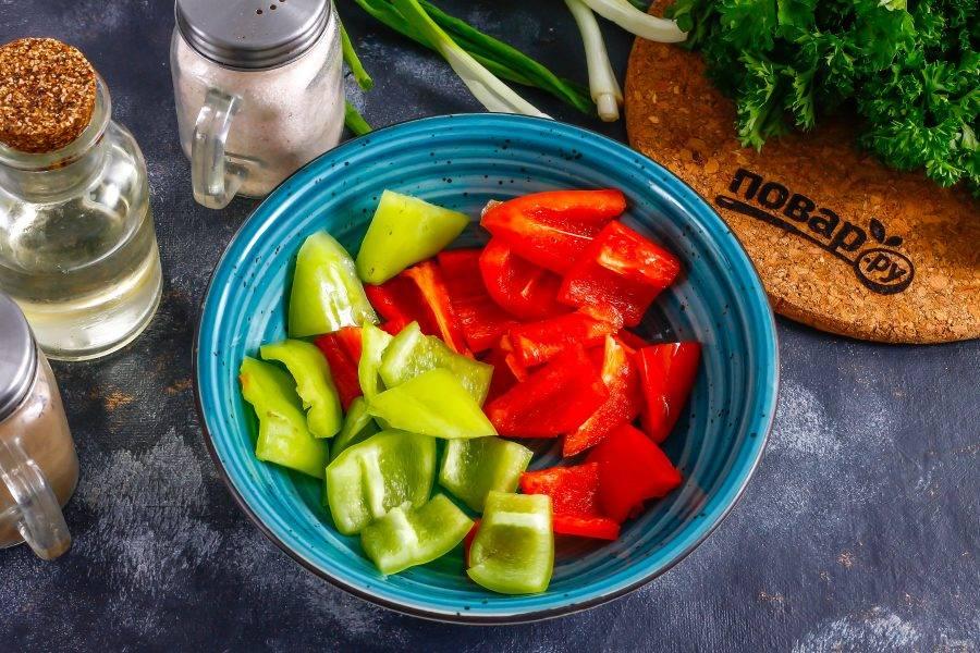 Промойте болгарский перец в воде, очистите от семян и нарежьте крупными кусочками. Высыпьте нарезку в глубокую емкость.