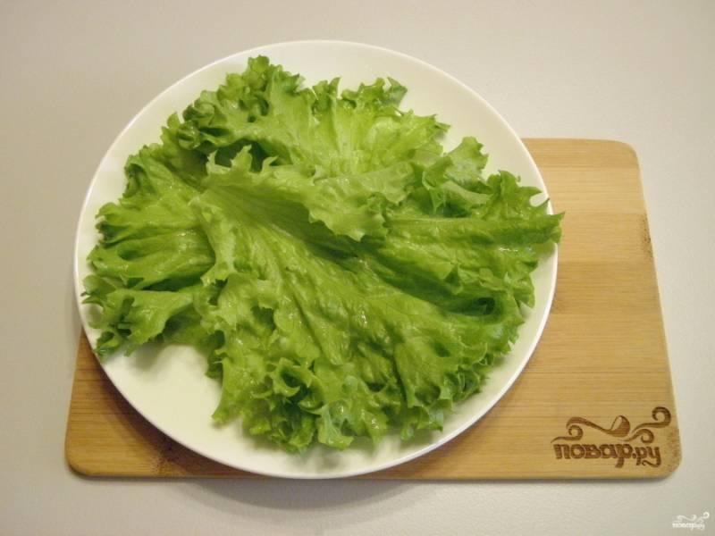 Возьмите порционные тарелочки, разложите листья салата. Из данного количества продуктов выходит две хорошие порции.