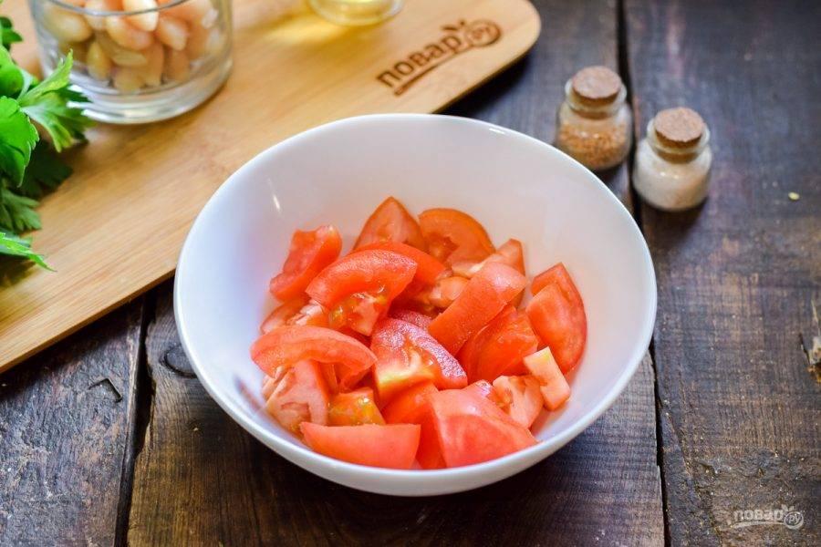 Помидоры ополосните и просушите, нарежьте небольшими кусочками и переложите в салатник.