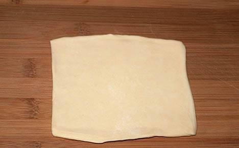 """Раскатайте слоеное тесто. Разрежьте его на квадраты (примерный размер — примерно 12*12 см.). Сторона квадрата должна быть чуть больше больше, чем сосиска, чтобы мы смогли в итоге обернуть ее тестом, как фантик — конфету. Можно использовать слоеное пресное тесто, но я для этого блюдо больше люблю брать дрожжевое, так как оно хорошо """"поднимается"""" при выпечке в духовке и становится хрустящим. Если у вас замороженное тесто, то обязательно предварительно разморозьте его."""