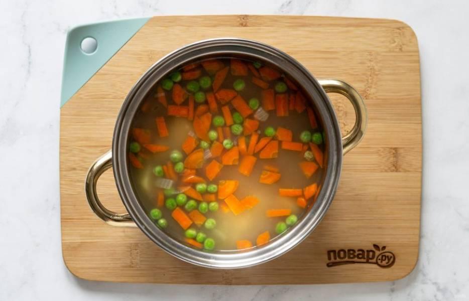 Добавьте замороженный зеленый горошек. Варите суп примерно 5 минут.