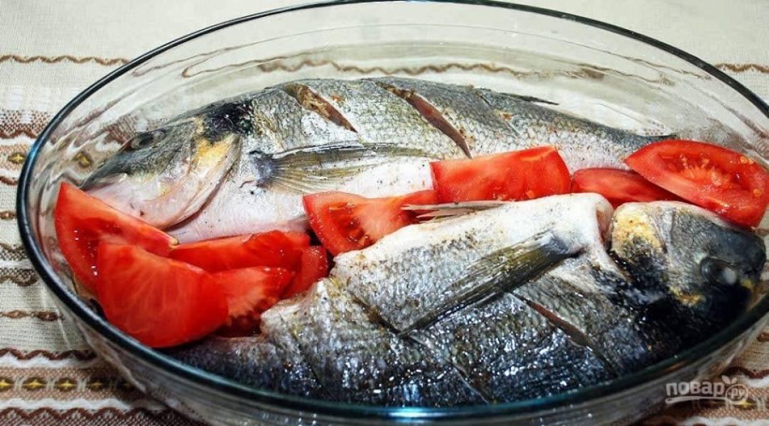 3. Перекладываем также помидорами все пустоты между рыбками и противнем. Поливаем соусом: лимонный сок смешаем со специями, маслом, измельченным чесноком. Поливаем сверху.