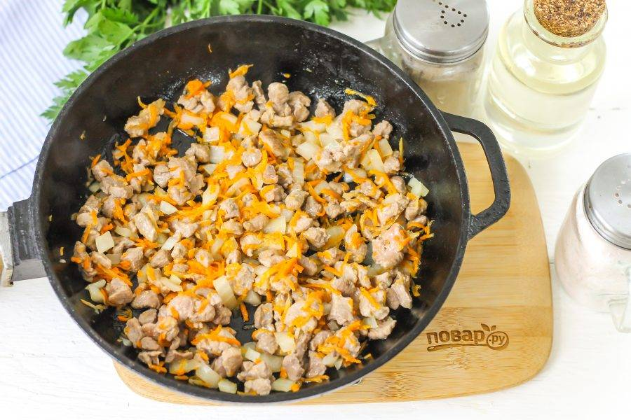 Обжарьте мясо до румяности в сковороде, влив в нее растительное масло. Добавьте овощные нарезки и обжарьте еще 2-3 минуты.