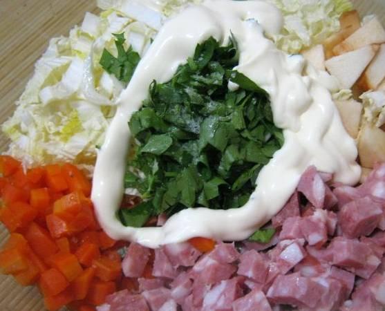 Теперь нужно нарезать кубиками: морковь, колбасу и яблоко. Складываем все в салатницу, добавляем нашинкованую капусту, измельченную зелень и майонез.