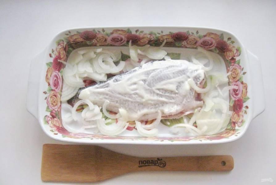 Репчатый лук нарежьте полукольцами и разложите вокруг рыбы.