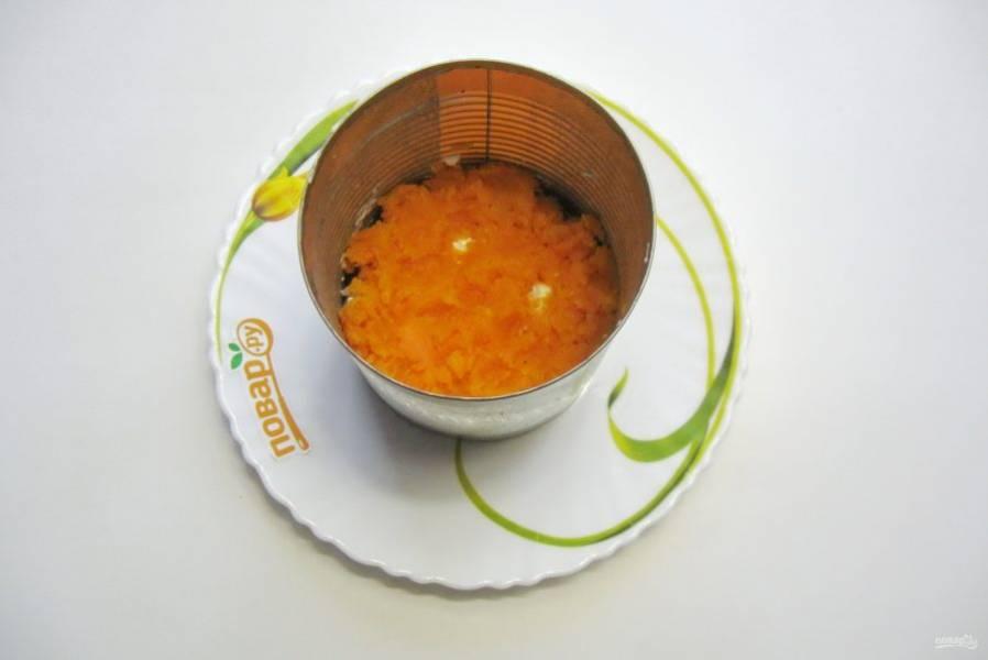 Морковь сварите, охладите, очистите и натрите на терке. Морковь - третий слой салата. Смажьте этот слой майонезом.