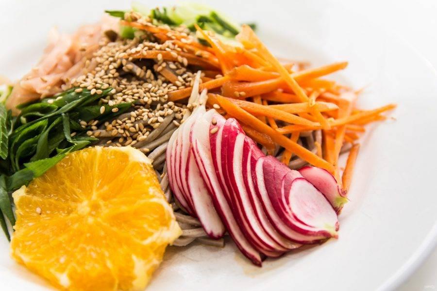 Теперь все овощи соединяем в салатнике, поливаем заправкой, солим и перчим по вкусу, присыпаем кунжутом. На порционные тарелки выкладываем понемногу лапши, наверх — овощи. Украшаем салат апельсином и подаем.
