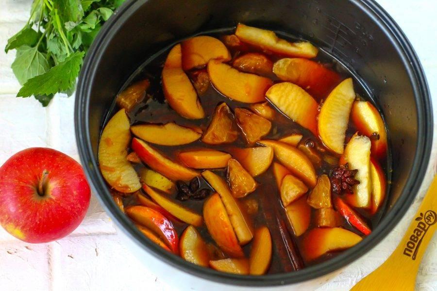 """Влейте яблочный сок и любое столовое красное вино. Добавляя крепленое вино, влейте немного горячей воды, чтобы снизить процент алкоголя. Активируйте на табло техники режим """"Варка"""" или """"Суп"""" на 5-10 минут, в зависимости от модели техники. Прогрейте вместе все компоненты практически до кипения, затем переведите мультиварку в режим подогрева на 10 минут. За это время фрукты протомятся и станут мягкими."""