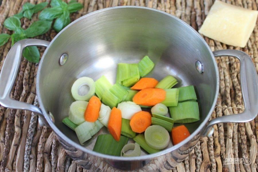 Лук-порей и морковь режем крупно и высыпаем в кастрюлю.