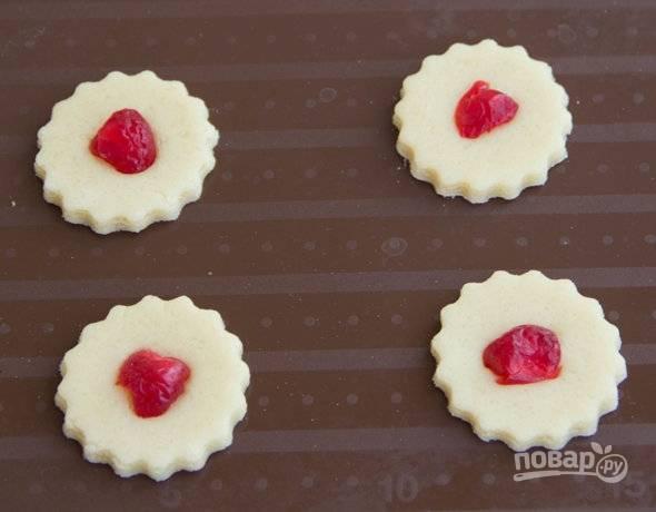 Раскатайте тесто не тонко. Вырежьте с помощью формочек печенье. Вставьте в центр по изюминке или вяленой вишне.  Разогрейте духовку до 200 С. Переложите печенье на противень. Выпекайте 10-15 минут.