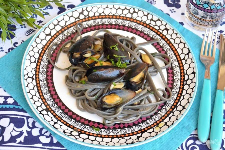 Подайте черные спагетти с мидиями в белом вине, посыпав мелко нарезанной зеленью петрушки.