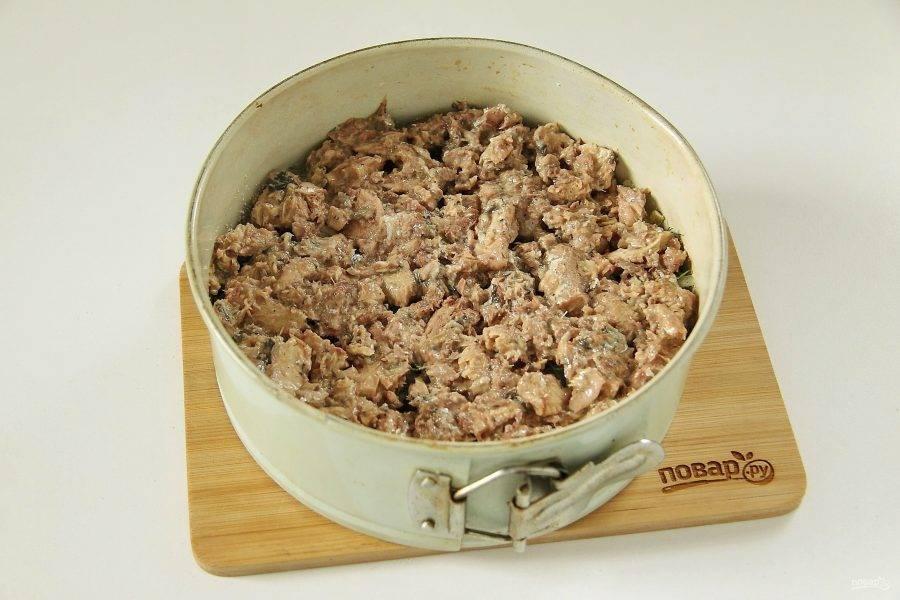 С рыбы слейте масло. Разомните ее вилкой и выложите ровным слоем на картофель с луком и зеленью.