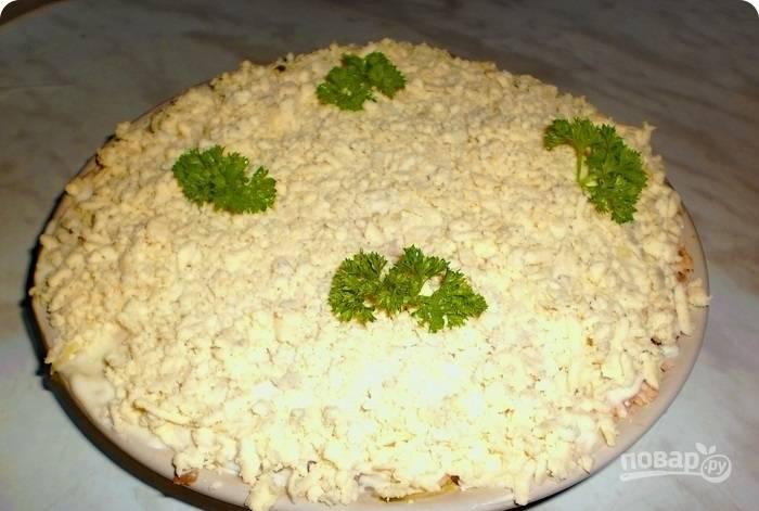 10.Желтки натираю на терке и посыпаю ими блюдо, украшаю петрушкой и настаиваю салат 20-30 минут в холодильнике.