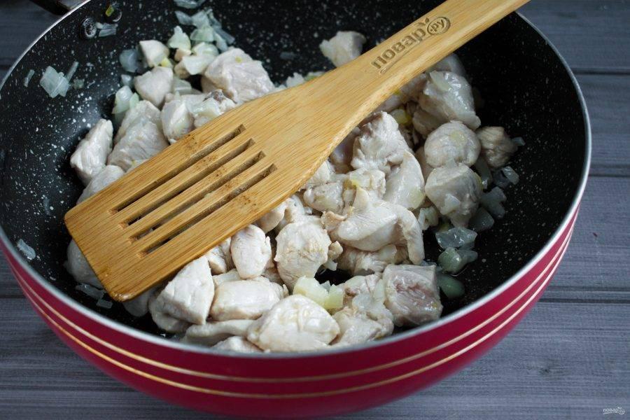 Куриную грудку нарежьте мелкими кусочками, добавьте к луку, обжаривайте до побеления.