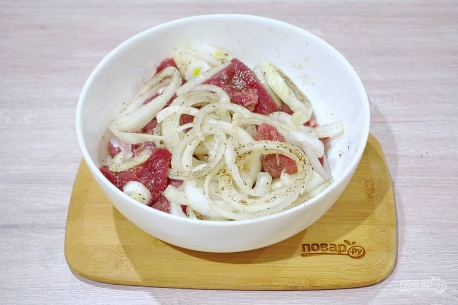 Смешайте лук, мясо и специи. Смешайте  несколько ложек растительного масла с уксусом. Влейте массу к мясу, хорошо перемешайте руками.