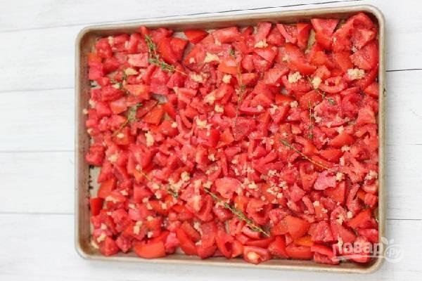 2. Помидоры вымойте, обсушите немного и нарежьте мелкими кусочками. При желании можно аккуратно удалить у них семена. Сбрызните оливковым маслом, добавьте измельченный чеснок. Посолите, поперчите по вкусу, добавьте травы для аромата.