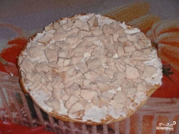 12. Когда все подготовительные этапы позади, можно начинать собирать блинный пирог с курицей и грибами в домашних условиях. Выложите блинчик, смажьте его кремом, распределите сверху немного курочки.