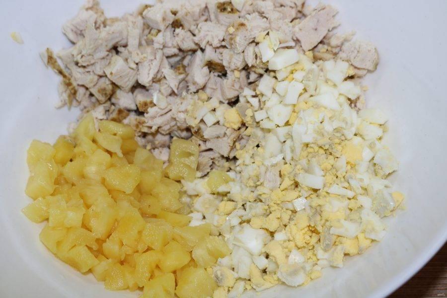 Яйца и ананас нарежьте кубиками, соедените всё.
