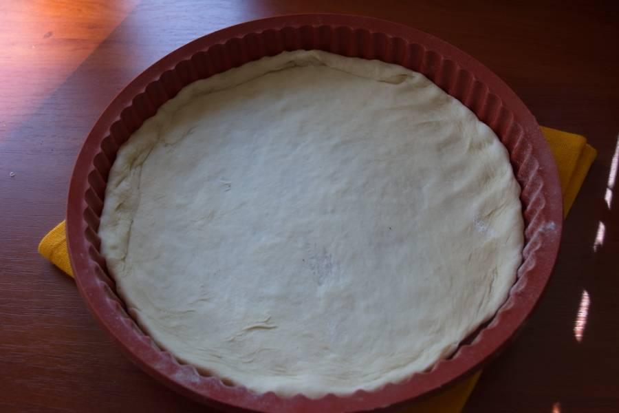 Тесто разделите на 2 части. Выложите в форму для запекания. Предварительно раскатайте его на столе в пласт. Так удобнее будет выкладывать. Я предпочитаю тонкий корж пиццы. Поэтому раскатываю тонко.