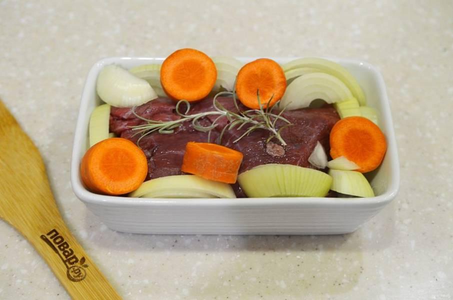 5. В жаропрочную форму выложите мясо, вокруг лук и морковь.