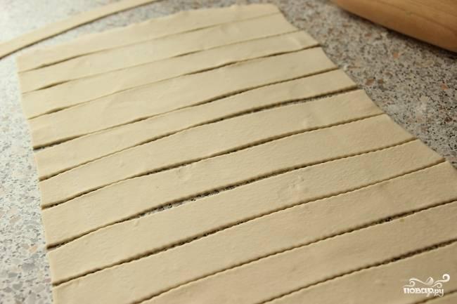 Заранее включите духовку, чтобы она хорошо прогрелась. Теперь приступайте к изготовлению заготовок для трубочек. Для этого тесто раскатайте потоньше и нарежьте полосами по 2-2,5 см.