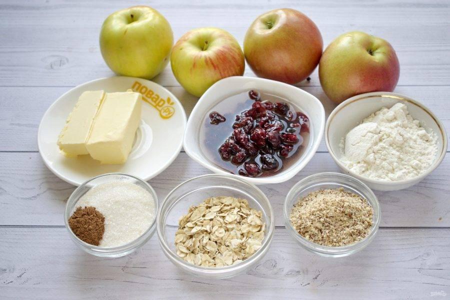 Подготовьте необходимые продукты. Орехи пробейте в блендере в крошку. Вяленую клюкву замочите в теплой воде на 10 минут.