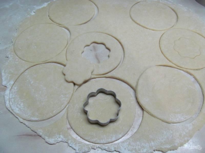 Выньте тесто из холодильника и раскатайте в тонкий пласт толщиной 0,3-0,5 см. При помощи кулинарного кольца или маленькой кофейной тарелки вырежьте кружки. Тесто, которое осталось невостребованным, нужно скатать в шар и раскатать еще раз в тонкий пласт. У половины кружков теста вырежьте середину при помощи формочек для печенья или маленькой рюмки.