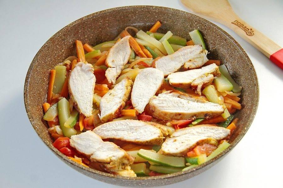 Накройте сковороду крышкой и тушите овощи на небольшом огне около 15 минут. Если будет недостаточно жидкости, влейте немного воды. Нарежьте куриное филе крупными ломтиками и добавьте в сковороду к овощам. Продолжайте тушить все вместе еще около 5 минут. Молодые кабачки с курицей готовы.
