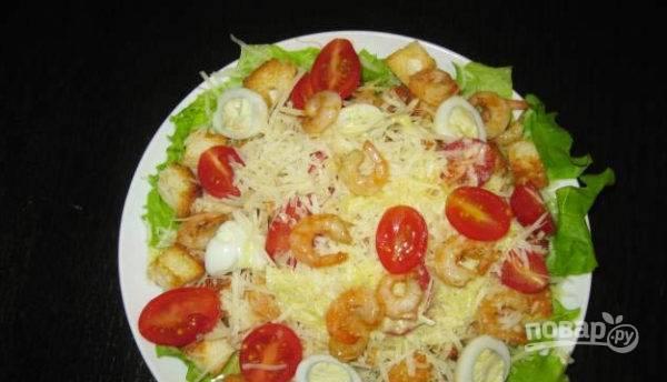 На плоскую тарелку выкладываем несколько листьев салата, на него выкладываем салат и украшаем по вкусу (можно половинками яйца, помидорками черри, креветками, сухариками).