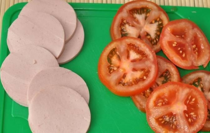 Нарезаем кружочками помидоры и колбасу.