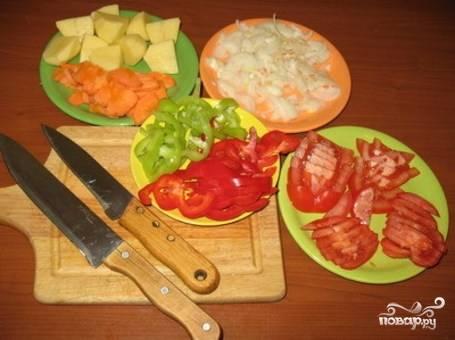 Нарежьте крупно картофель, а остальные овощи – полукольцами.