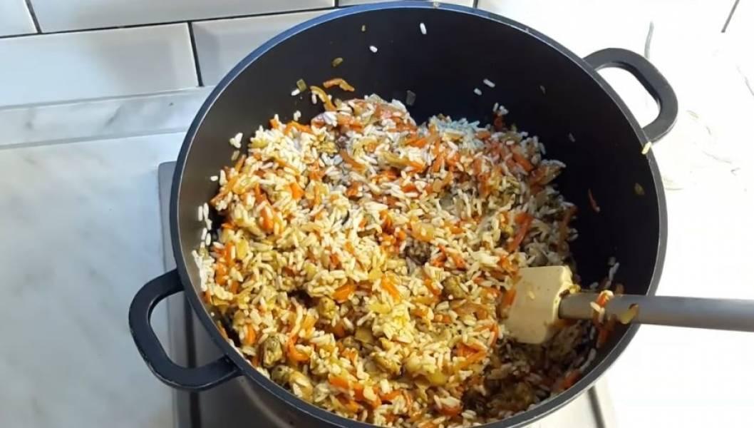 4. Хорошо все перемешайте и небольшими частями добавьте отваренный рис. Хорошо перемешивайте блюдо, чтобы все ингредиенты равномерно распределились. Добавьте чеснок и мелко порезанную зелень.