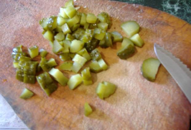 Шинкуем мелко капусту. Огурцы и картофель рубим маленькими кубиками. Выкладываем в большую кастрюлю, добавляем маслины, заливаем рассолом, кладем лавровый лист. Засыпаем сахаром и 1 ст.ложкой соли, тщательно перемешиваем, ставим на огонь. Если жидкости совсем мало, заливаем немного бульоном. Тушим, пока не приготовятся капуста с картофелем.