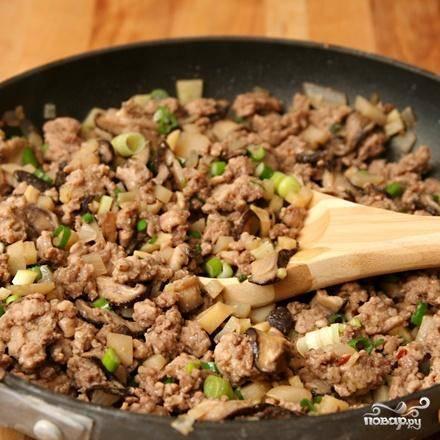 2. Разогреть масло в сковороде на среднем огне. Добавить лук-шалот, чеснок и имбирь. Жарить, постоянно помешивая, до появления аромата, около 1 минуты. Добавить грибы и щепотку соли, жарить, помешивая, пока грибы не станут мягкими. Добавить мясо с маринадом и водяные каштаны. Готовить, разминая мясо на маленькие кусочки, около 6 минут. Перемешать с зеленым луком.