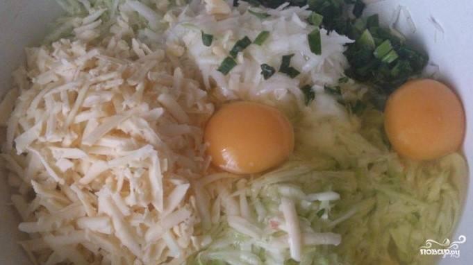 2. Натрите сыр. Порежьте мелко зеленый лук. Соедините их с тертым картофелем и кабачками. Вбейте яйца.