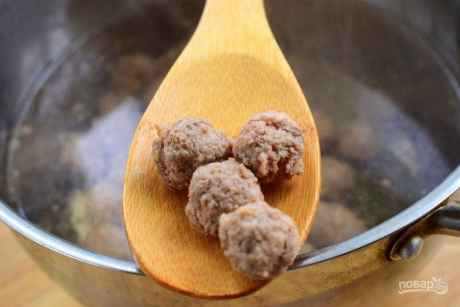В кастрюлю налейте немного воды, добавьте лавровый лист, душистый перец и веточку чабреца, доведите до кипения. Лук и чеснок  измельчите, половину добавьте в фарш, тщательно перемешайте и отбейте. Слепите из фарша шарики, отварите их до готовности в кипящей воде.