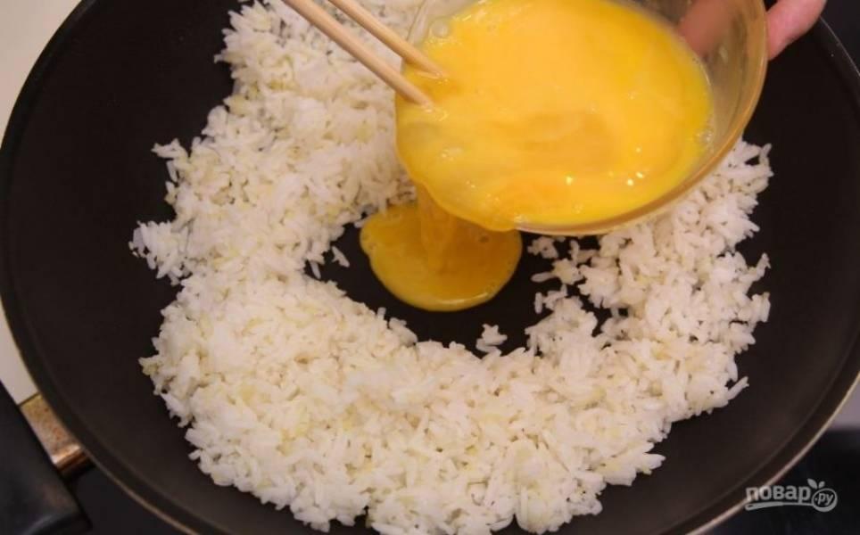 В углубление в рисе добавьте взбитые яйца и перемешайте смесь до однородности.