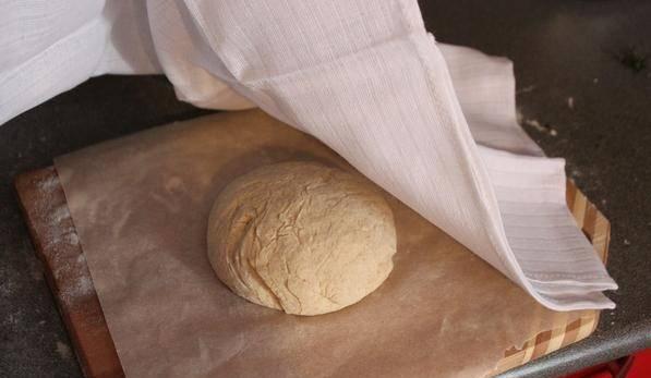 Присыпьте поверхность мукой и замесите тесто, добавляйте пшеничную муку, пока тесто не начнет отлипать от рук. Миску смажьте растительным маслом и оставьте тесто на час под крышкой. Сформируйте из теста шарики и оставьте на бумаге для выпекания под полотенцем на 1 час. Тесто поднимется.