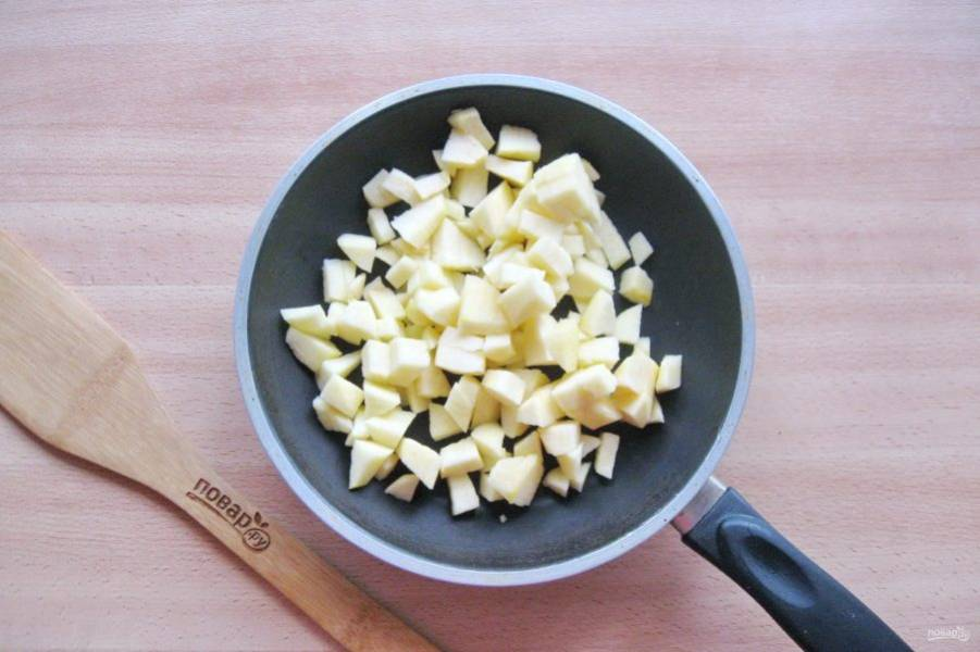 Сделайте начинку из яблок. Фрукты помойте, очистите, удалите семечки и нарежьте мелкими кубиками. Выложите в сковороду.