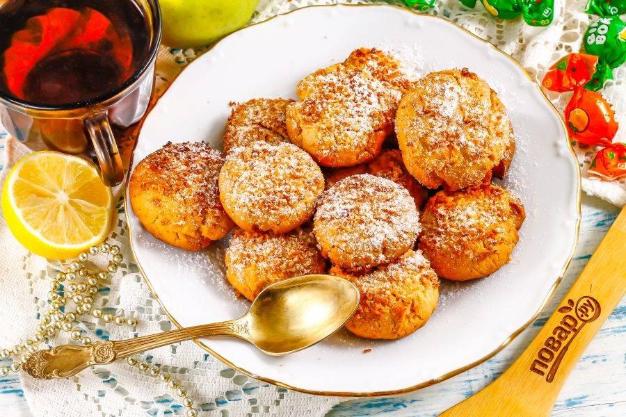Выложите печенье с кокосовой стружкой на тарелку и присыпьте сахарной пудрой, если она есть у вас в наличии.