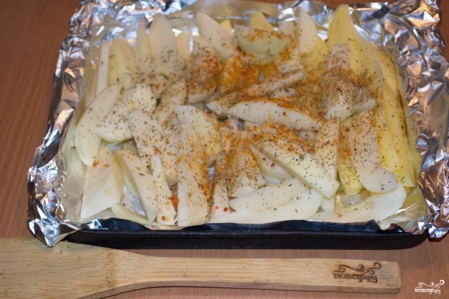 Картофель уложите на противень. Посыпьте специями и солью. Перемешайте. Добавьте немного растительного масла.