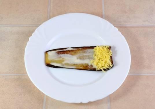 Смазываем каждую пластинку баклажана смесью из майонеза и чеснока, на верх выкладываем тертый сыр.