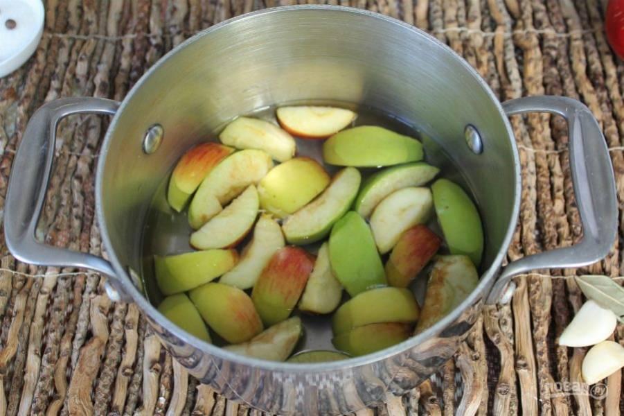 В кастрюлю наливаем воду. Яблоки нарезаем дольками, сердцевину удаляем. Яблоки кладем в кастрюлю.