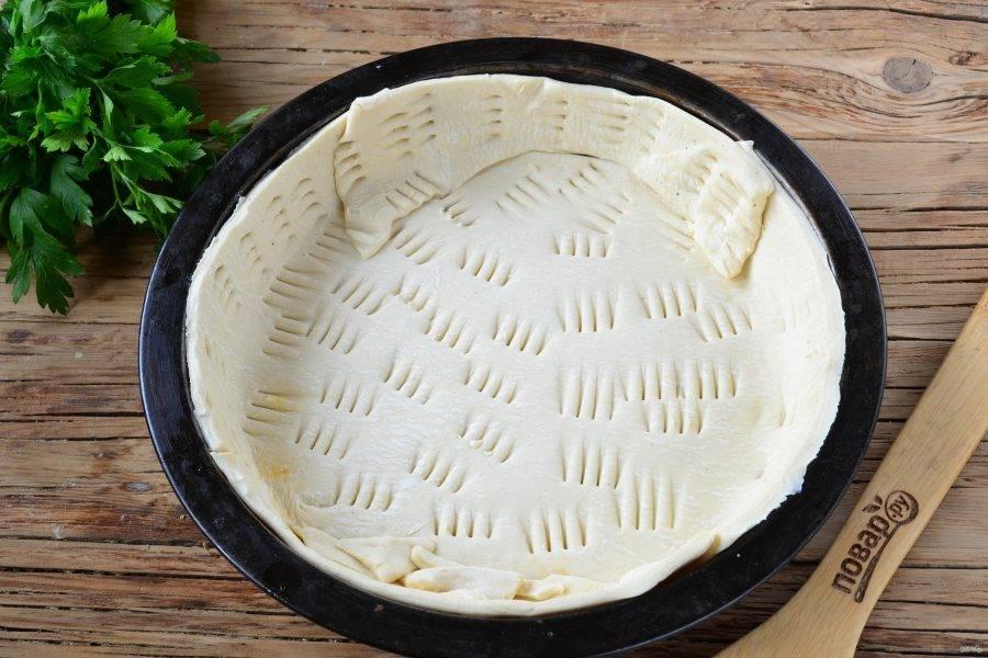Тесто раскатайте тонко, вложите тесто в круглую форму для выпечки, лишние части отрежьте и положите в те места, где теста не хватает. Тесто наколите вилкой и отправьте в духовку на 15-20 минут (температура 180 градусов), чтобы оно подзолотилось.